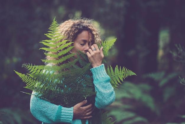 Sauvez la planète terre et célébrez le jour de la terre avec une femme adulte dans ses bras et tenez une feuille verte dans le bois de la forêt en profitant de la nature - arrêtez le concept de déforestation avec des gens qui aiment la nature