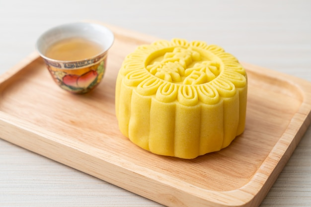 Saveur de crème de gâteau de lune chinoise avec du thé sur une plaque de bois