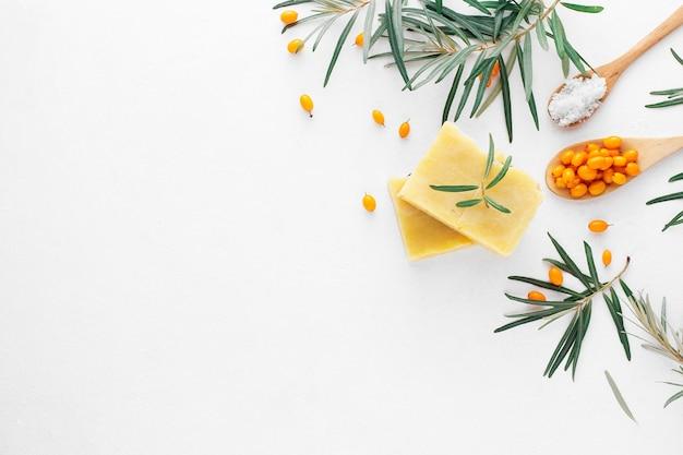 Savon à l'argousier naturel fait à la main avec des ingrédients sur blanc. vue de dessus, copiez l'espace.