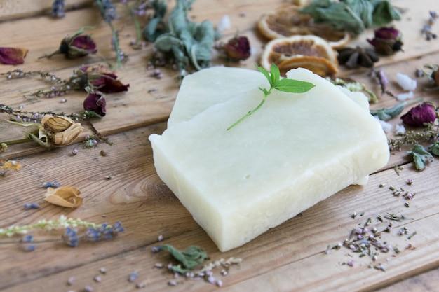 Savon artisanal aux herbes sur table en bois, soft focus