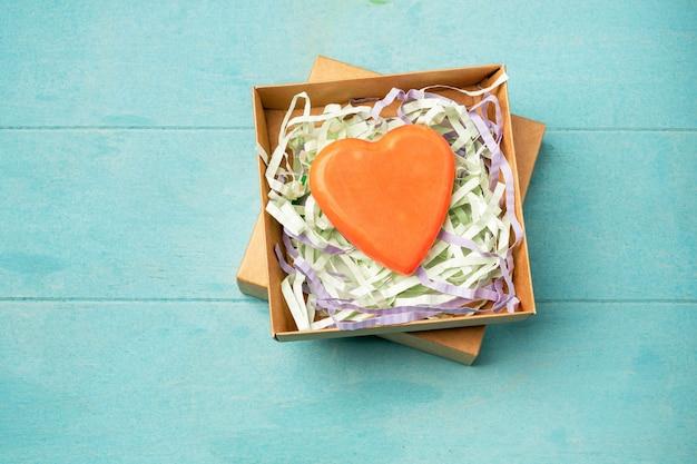 Savon artisanal à base d'ingrédients naturels sous forme de cœur dans une boîte cadeau.