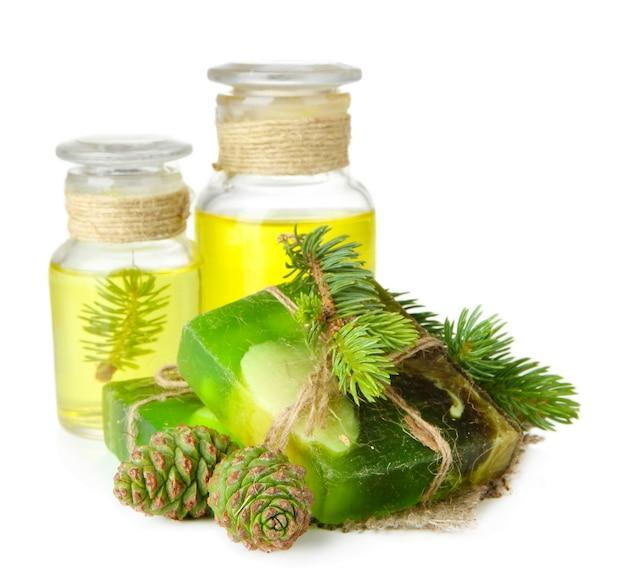 Savon artisanal et bouteilles d'huile de sapin, isolés sur blanc