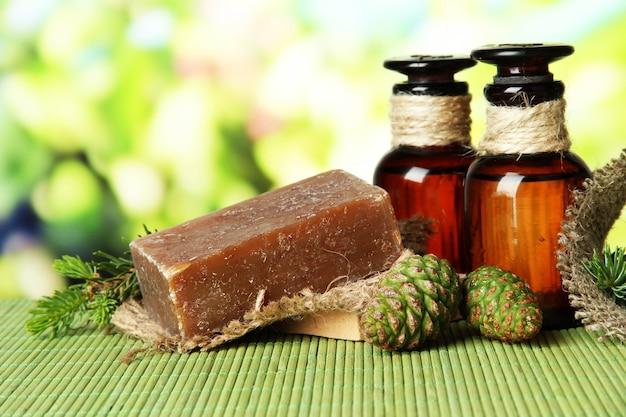 Savon artisanal et bouteilles d'huile de sapin sur tapis de bambou