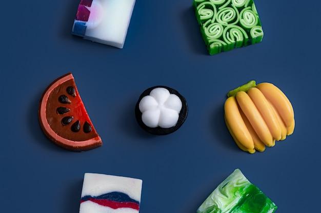 Savon artisanal brillant sous forme de fruits sur bleu.