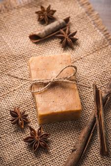 Savon artisanal à l'étoile de cannelle et d'anis sur fond de bois.