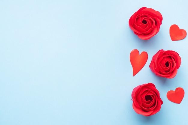 Savon artisanal en forme de rose, fleur rose rouge sur fond bleu. vue de dessus, minimaliste, espace copie.