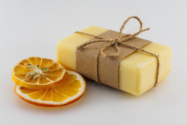 Savon artisanal jaune et tranches d'orange sèches sur fond blanc