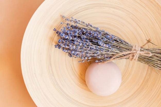Savon artisanal à la lavande. barre de savon naturel en forme de boule avec des fleurs de lavande séchées sur une plaque en bois. cosmétique bio pour soins de la peau et spa