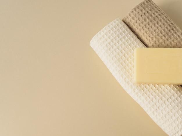Savon artisanal et serviettes sur beige.