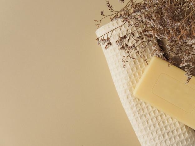 Savon artisanal, serviettes et fleurs séchées sur fond beige.