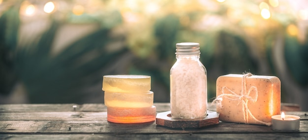 Savon artisanal spa au sel de mer, composition sur feuilles tropicales avec une bougie, table en bois