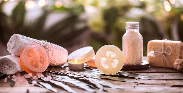Savon artisanal de spa avec des serviettes blanches et du sel de mer, la composition des feuilles tropicales avec une bougie, table en bois