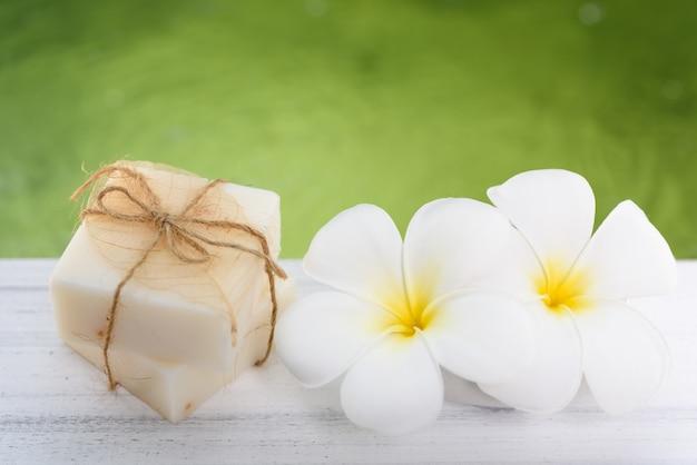 Savon au lait de spa et fleurs de frangipanier sur table en bois blanc