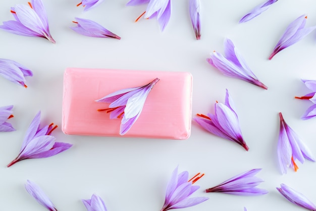 Savon au safran et beaucoup de belles fleurs de crocus violet sur blanc