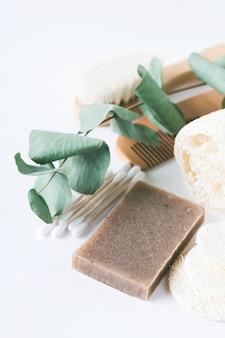 Savon bio écologique, brosses à dents en bambou, gant de toilette, peigne, luffa et branche d'eucalyptus isolé sur une surface blanche. copiez l'espace.