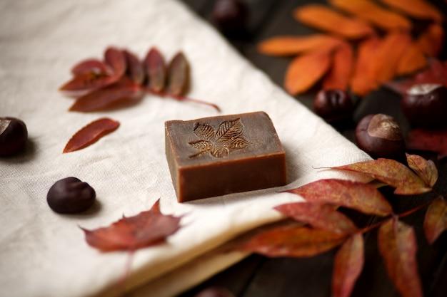 Savon bio sur le lin contre les feuilles d'automne et fond en bois, close up
