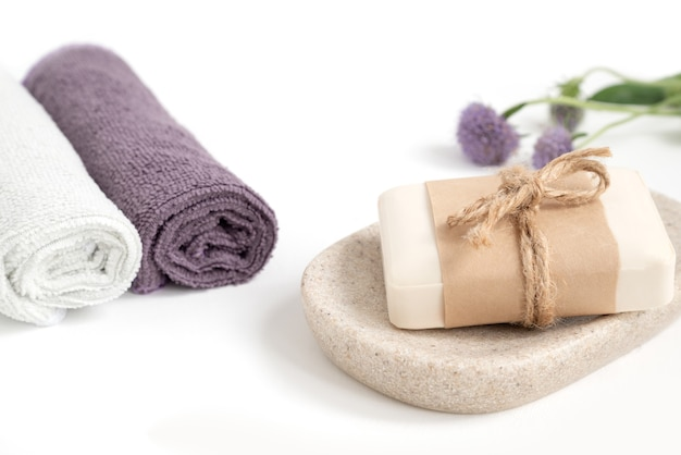 Savon bio sur plateau avec fleur violette en fleurs avec serviettes colorées roulées sur table de salle de bain