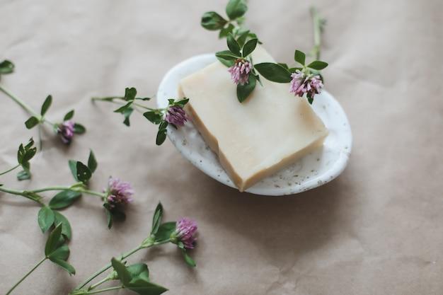 Savon biologique de spa naturel fait à la main avec des fleurs sur un porte-savon en céramique sur fond de papier artisanal haut vi ...