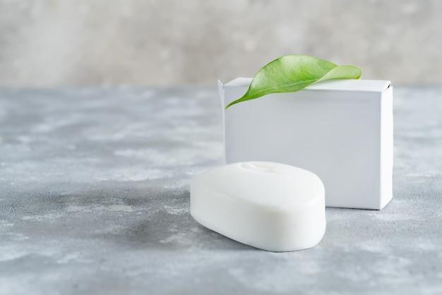 Savon blanc pour main avec feuille sur fond de pierre. maquette pour le logo et le texte.