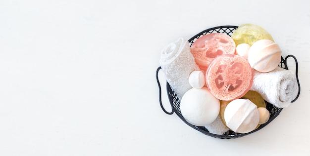 Savon, bombes de bain et serviette dans le panier sur le tableau blanc. concept de beauté et de soins du corps.