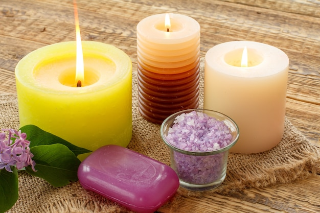 Savon, bougie allumée, bol avec sel de mer et fleurs lilas sur planches de bois. produits et accessoires de spa.