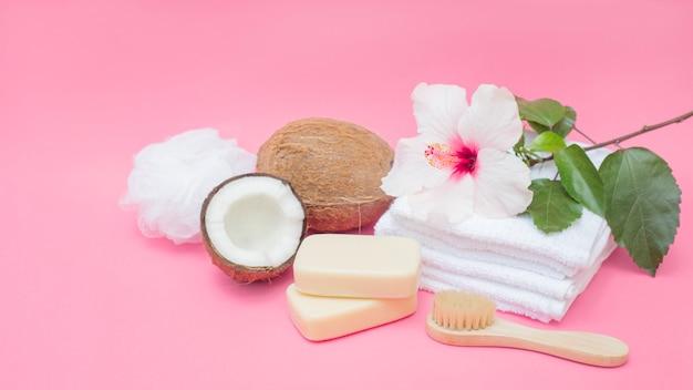 Savon; brosse; noix de coco; éponge; fleurs et serviettes sur fond rose