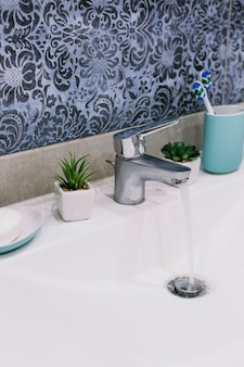 Savon et brosses à dents près du robinet