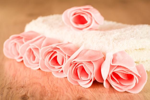 Savon en forme de roses et une serviette sur un fond en bois
