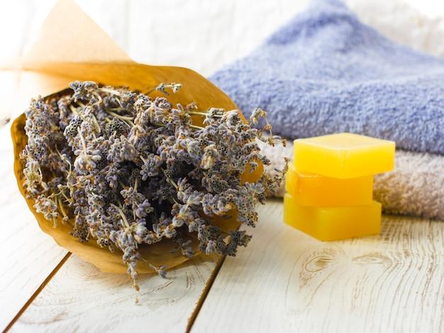 Savon à la lavande naturelle et sel de bain, huile française et serviettes sur un fond en bois blanc