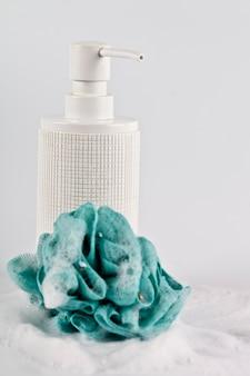 Savon liquide, éponge verte et mousse sur une surface claire.