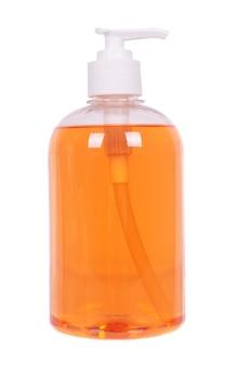 Savon liquide orange dans une bouteille, isolé sur un espace blanc.