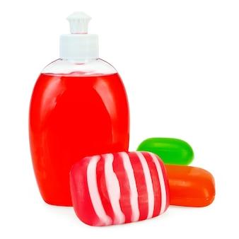 Savon liquide rouge dans une bouteille, savon solide rouge, vert et rayé isolé sur fond blanc