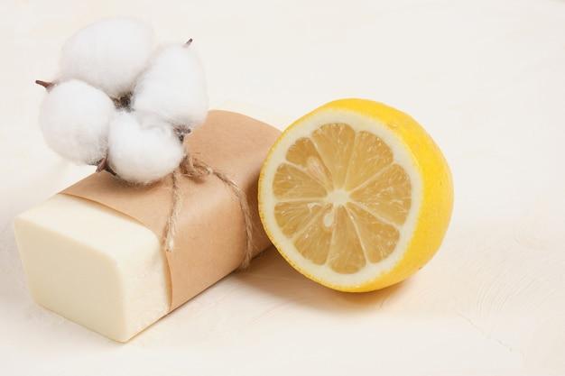 Savon maison parfumé au citron avec fleur de citron et de coton sur fond clair espace de copie