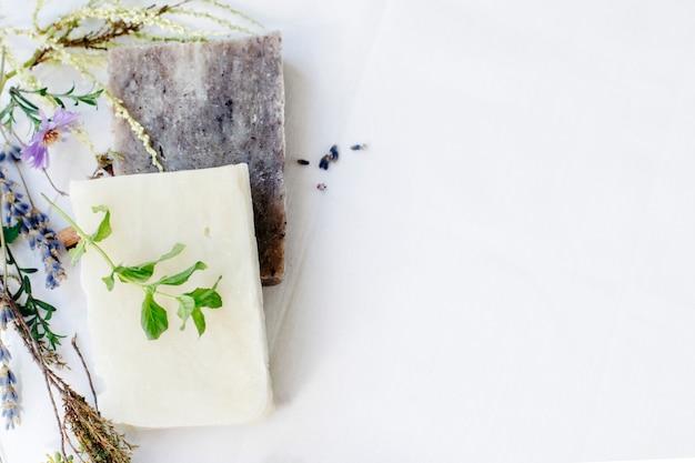 Savon naturel aux herbes pour les soins de la peau sur fond blanc, vue de dessus, espace copie