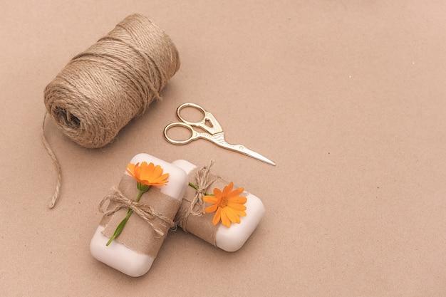 Savon naturel fait à la main, décoré avec du papier kraft, des fleurs de calendula orange, un écheveau de ficelle et des ciseaux. cosmétique bio