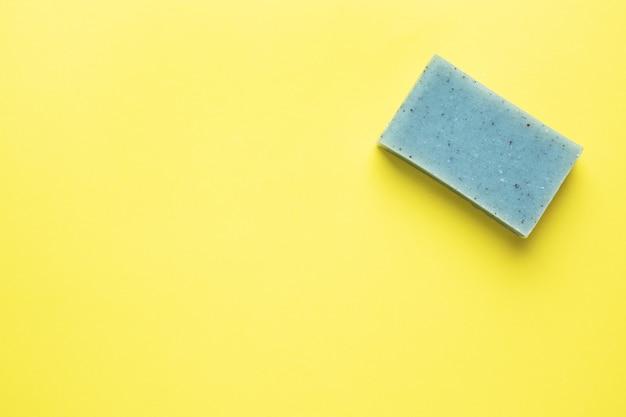 Savon naturel sur fond jaune. à plat, le concept de propreté des mains au spa. copie espace
