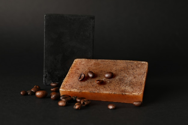 Savon naturel et graines de café sur une surface noire