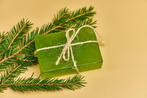 Savon de pin fait à la main avec des branches d'aiguilles sur une surface beige