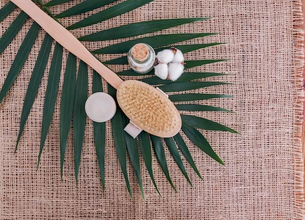 Savon, sel de mer en bouteille de verre, pinceau naturel et fleur de coton sur feuille de palmier