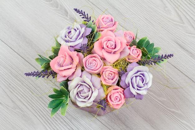 Savon sous forme de différentes fleurs colorées sur le fond en bois gris. vue de dessus.