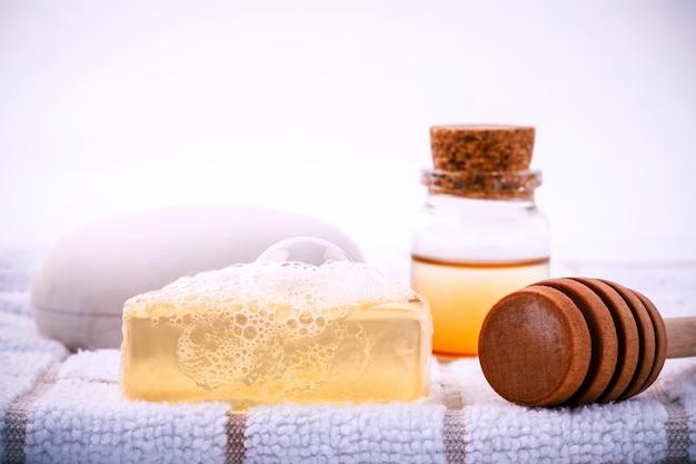 Savon de spa à base de plantes sur une serviette de bain blanche avec du miel isoler sur fond blanc.
