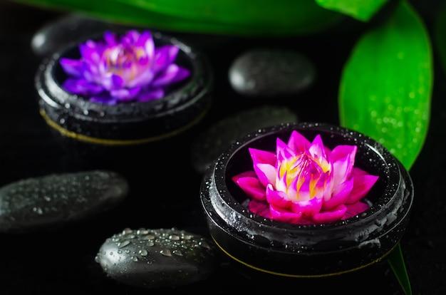 Savon spa avec de l'eau forme de fleur de lilly sur fond noir avec des pierres et des gouttes d'eau