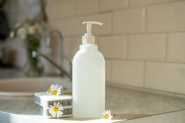 Savon à vaisselle écologique non toxique avec fleurs de camomille, assiettes blanches propres. photo de haute qualité