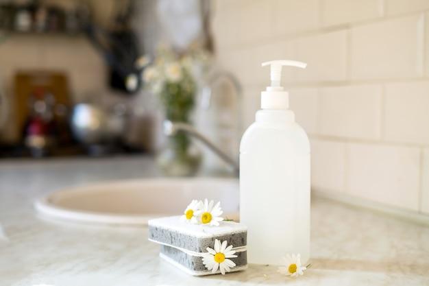 Savon à vaisselle écologique non toxique avec des fleurs de camomille pour nettoyer les assiettes blanches
