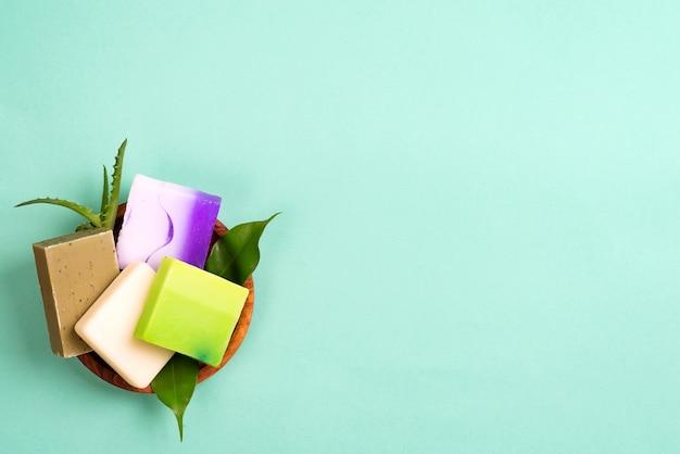 Savons de bar faits maison bio colorés à la main dans un panier avec des feuilles sur le vert