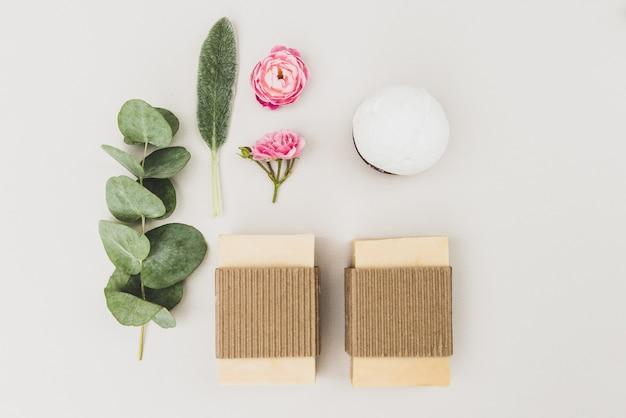 Savons bio faits à la main, branche de fleurs de rose d'eucalyptus et sel de mer pour les traitements de spa sur fond blanc, vue du dessus