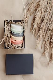 Savons naturels ronds faits à la main dans une boîte cadeau noire vue de dessus couleurs pastel naturelles