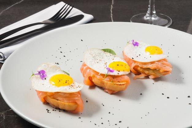 Savoureuse bruschetta au saumon et oeuf sur une assiette sur un fond sombre