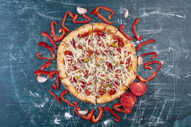 Savoureuse pizza au fromage sur bleu avec des légumes frais.