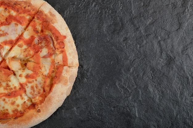 Savoureuse pizza au poulet buffle épicé sur une surface noire.